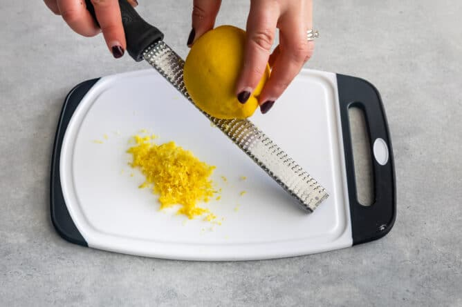 Overhead shot of lemon being zested over a cutting board