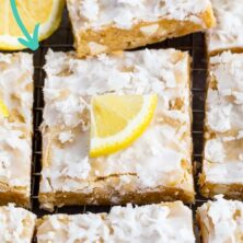 Overhead shot of lemon coconut blondie squares on a wire cooling rack with lemon wedges on top and recipe title on top of image