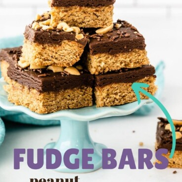 Peanut butter cookie fudge bars cut into squares and placed on a turquoise cake stand and recipe title on image