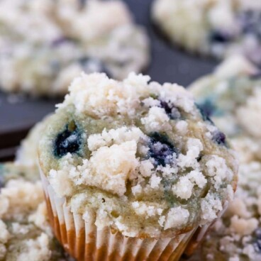 blueberry muffin sitting on stack of muffins with words on photo