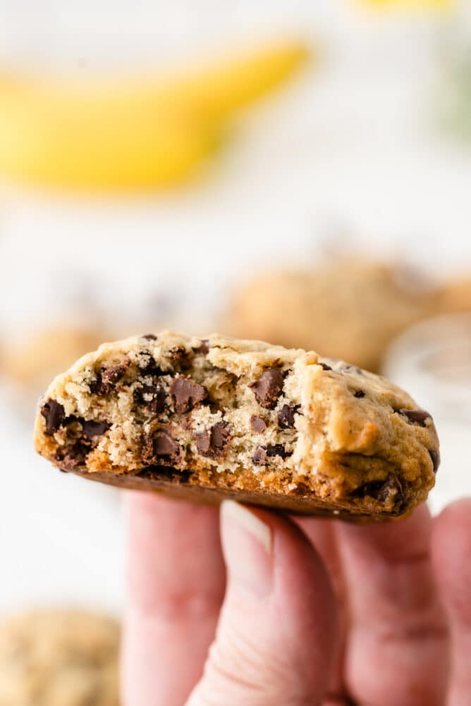 Hand holding a banana chocolate chip cookie that's cut in half
