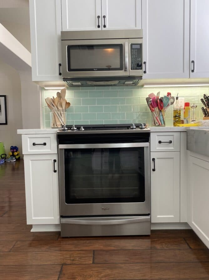 oven in kitchen with white cabinets and green backsplash