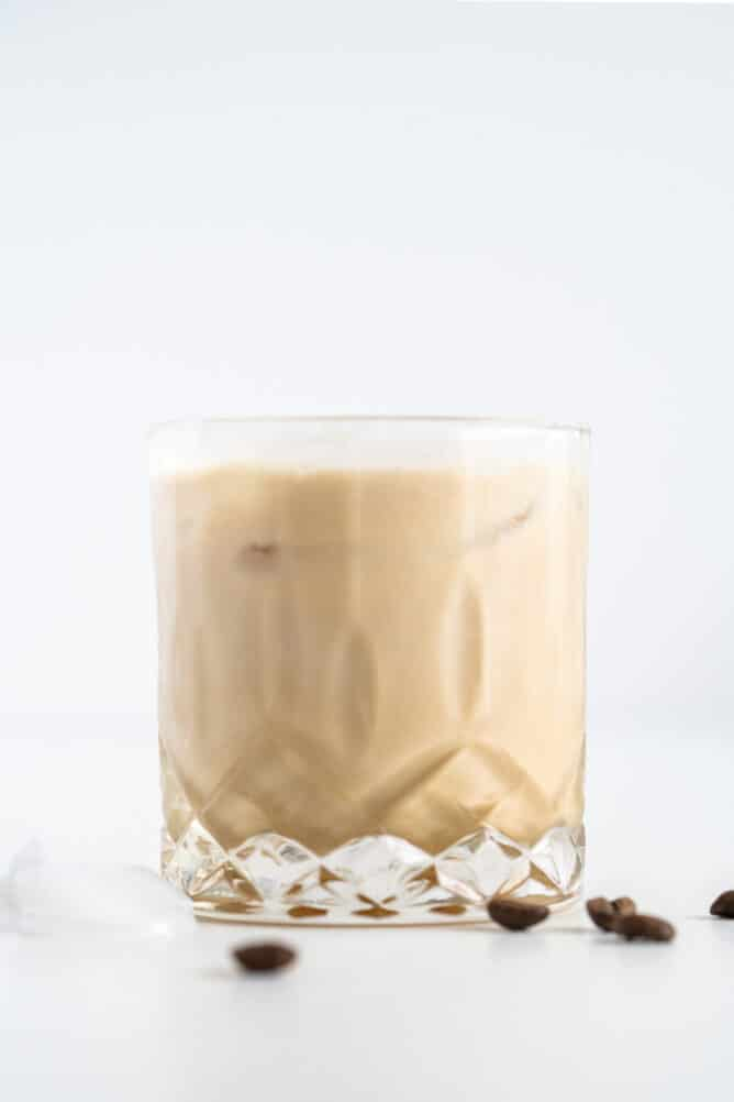 Side shot of white russian in a cocktail glass with coffee beans around it