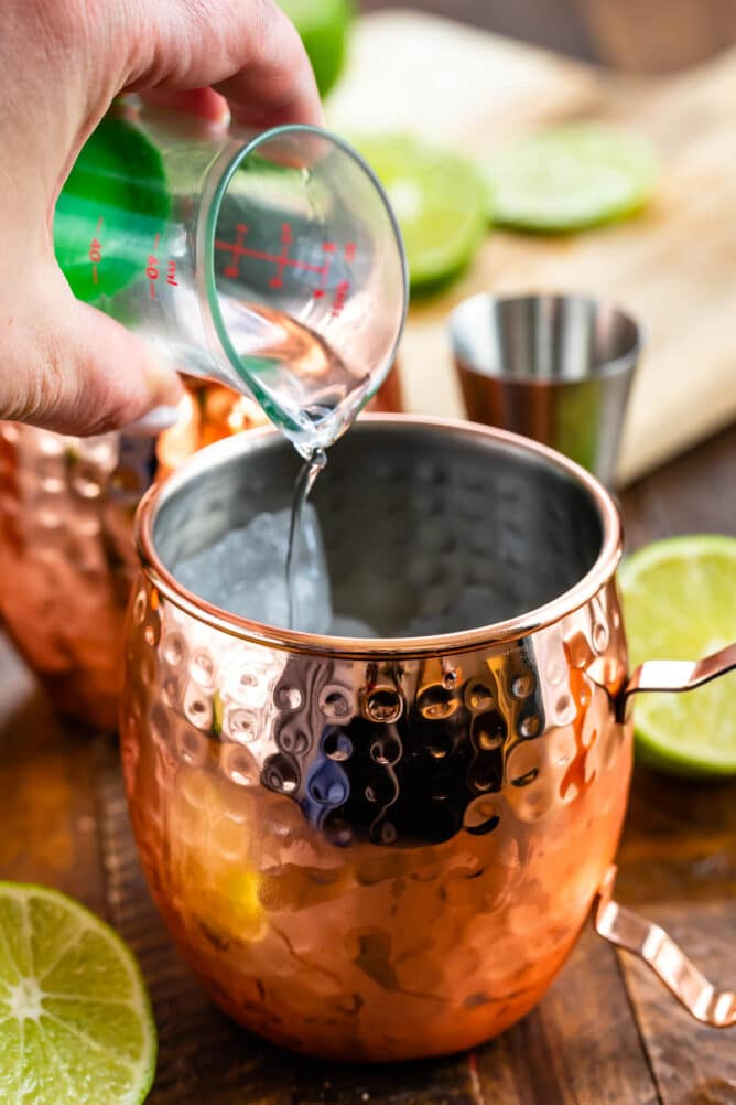 Shot of vodka being poured into a moscow mule mug