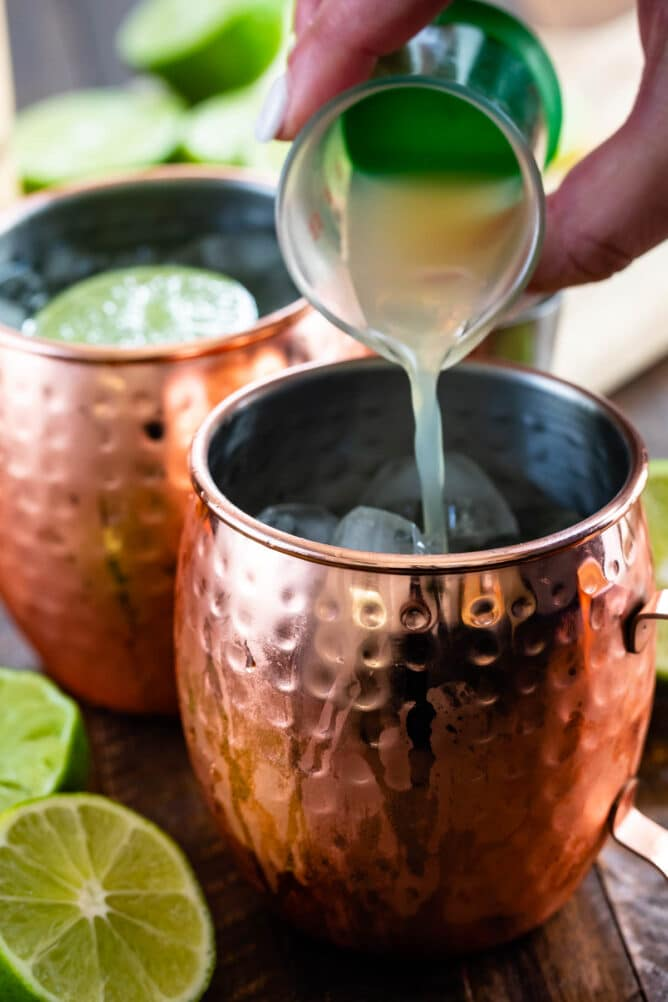 Lime juice being poured into a moscow mule mug