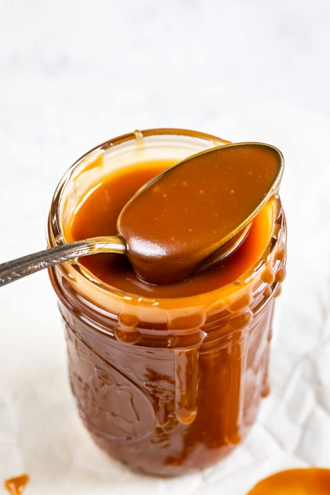 Spoonful of easy caramel sauce coming out of mason jar of sauce