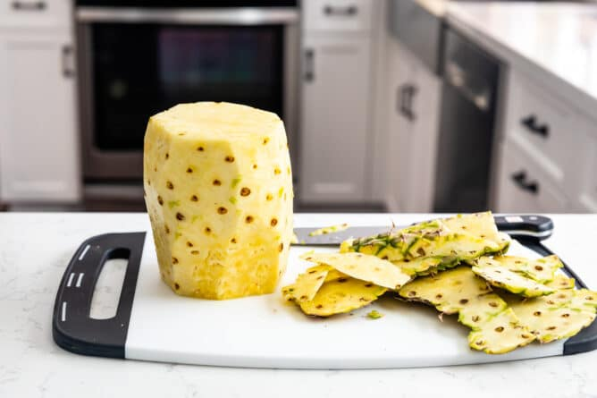 pineapple without skin on white cutting board with scraps next to it
