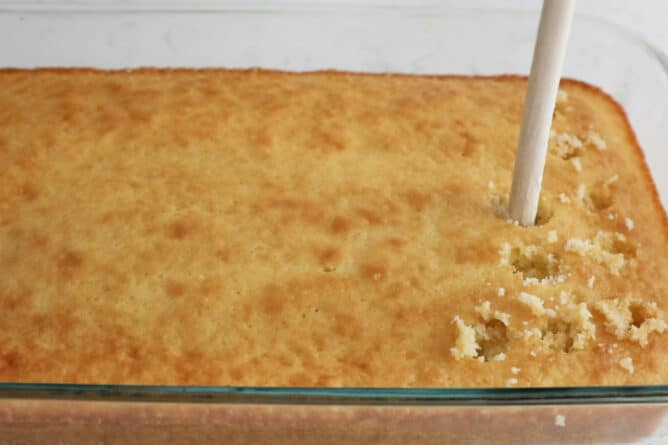 cake in pan being poked with wooden spoon