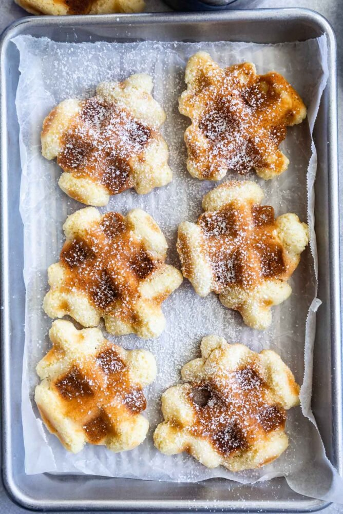 Overhead view of six waffle cookies sprinkled with powdered sugar on a baking sheet