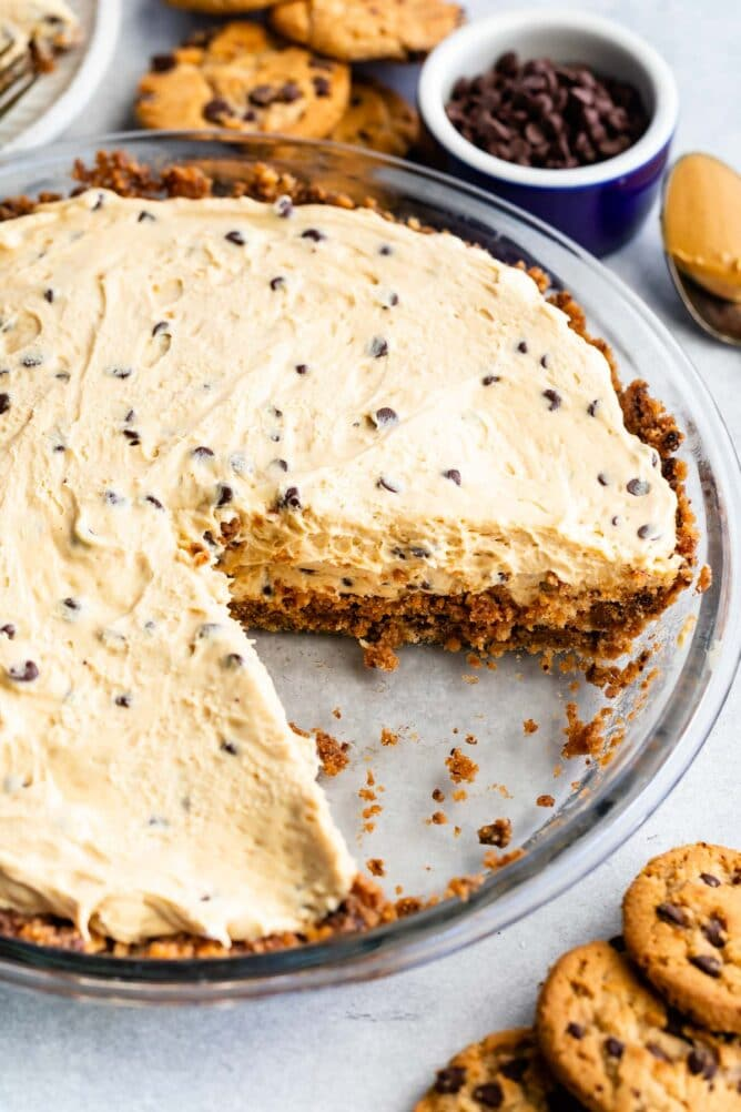 Close up overhead shot of chocolate chip peanut butter pie with one slice missing and chocolate chip cookies around the pie