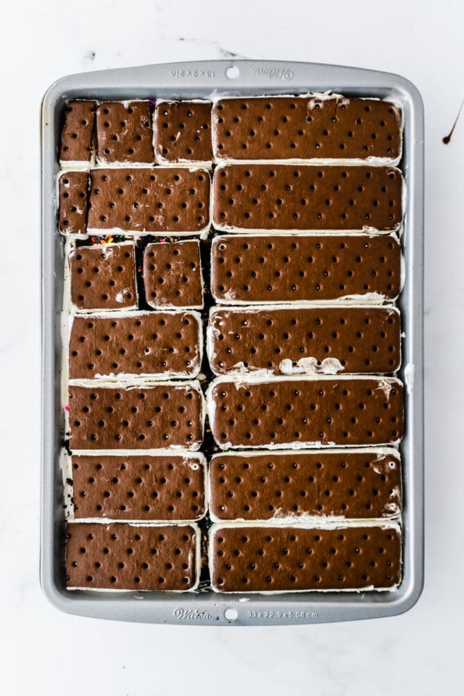Overhead process shot showing ice cream sandwiches layered in cake pan