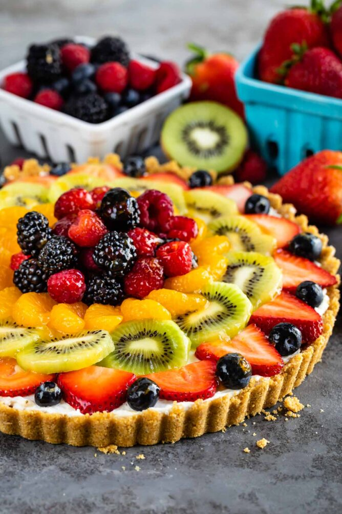 Side shot of no bake fruit tart with lots of fruit in the background