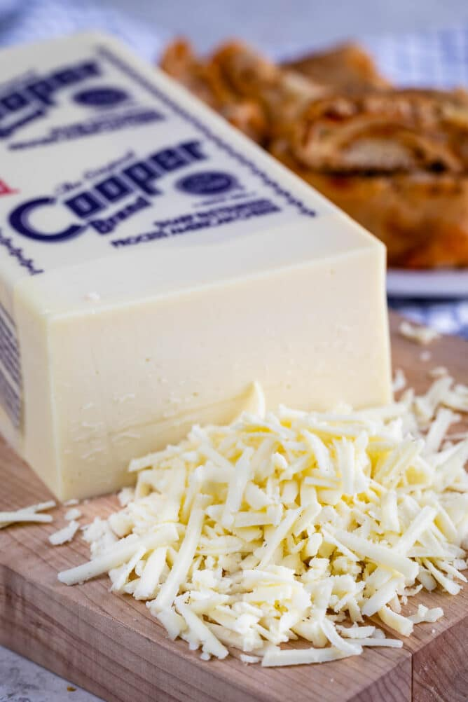 block of Cooper cheese with shredded cheese in front
