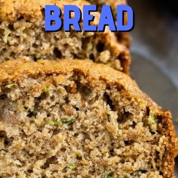 One loaf of zucchini bread with half cut into bread slices with recipe title on top of image