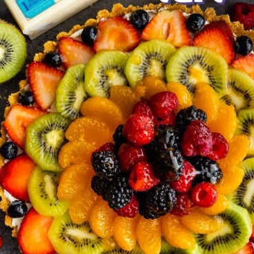 Overhead shot of no bake fruit tart with ingredients around it and recipe title on top of photo