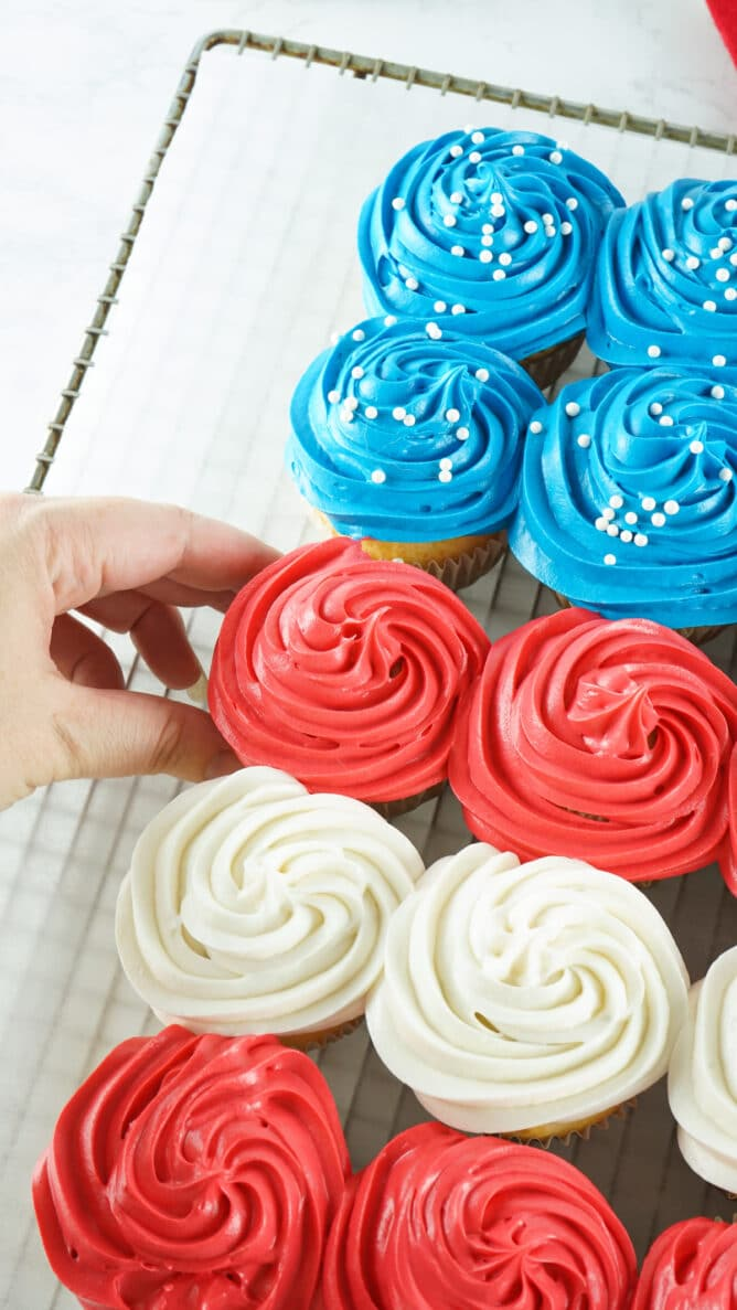 Hand reaching for a red cupcake from the side of the american flag cupcake cake