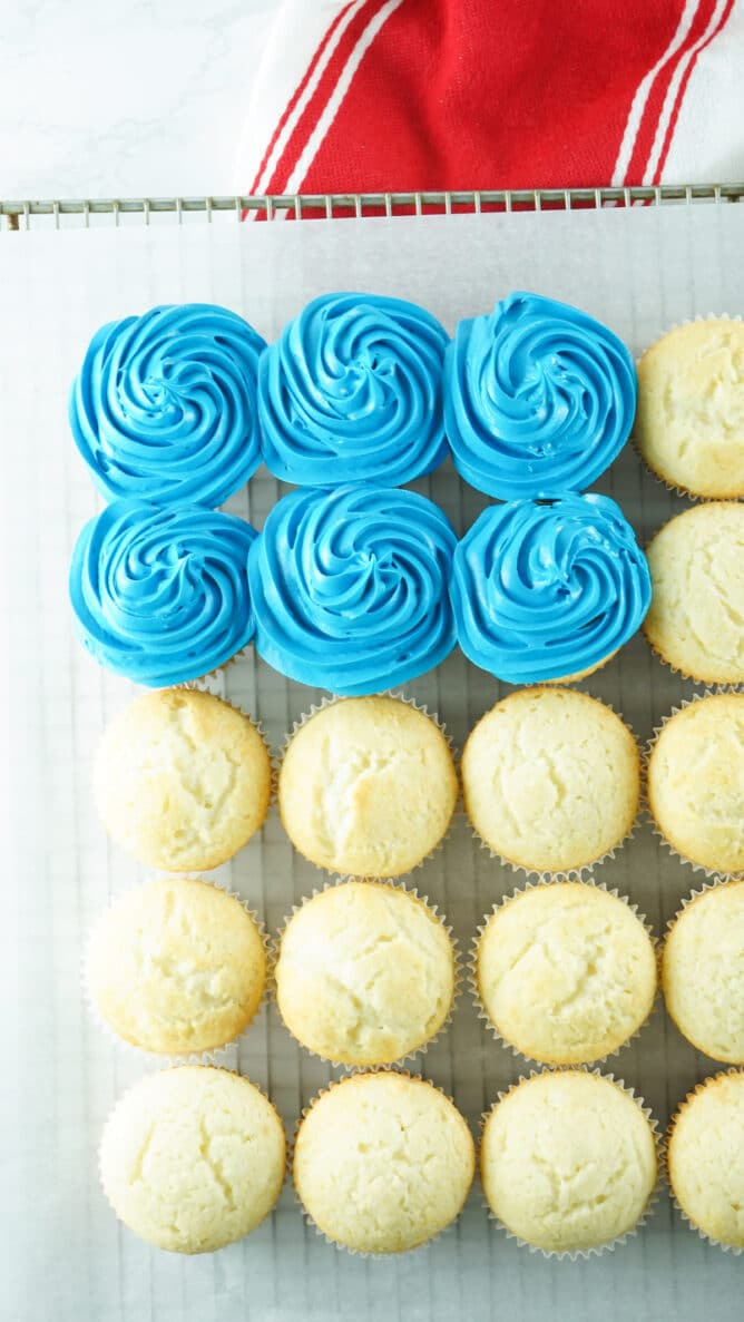 Overhead shot of top left corner of american flag cupcake cake with six cupcakes iced in blue frosting
