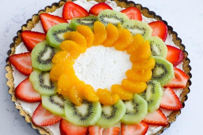 No bake fruit tart topped with strawberries, kiwis and oranges