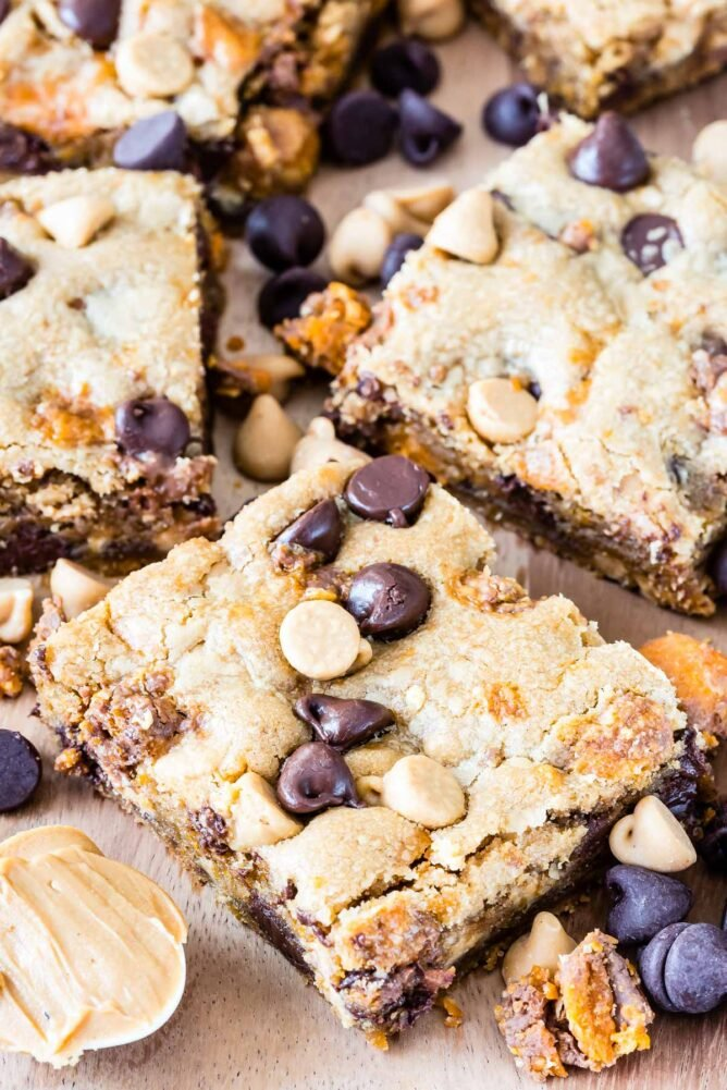 Peanut butter cookie bars cut into squares with mix-ins all around
