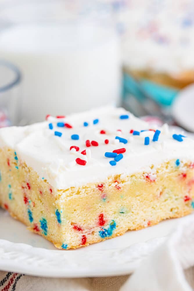 cookie bar with frosting and sprinkles on white plate
