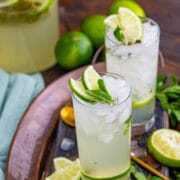 Two glasses of mojitos with lime and mint around them