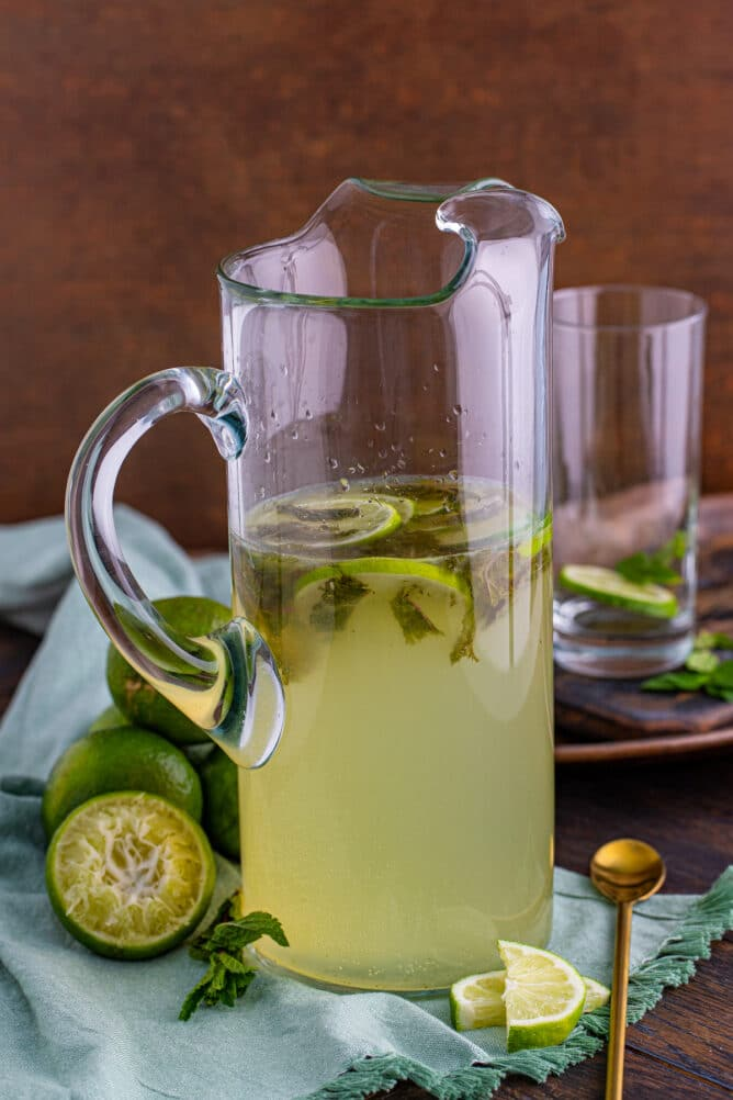 Pitcher of mojitos with ingredients around it