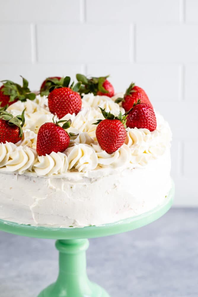 cake on mint cake plate with fresh strawberries on top
