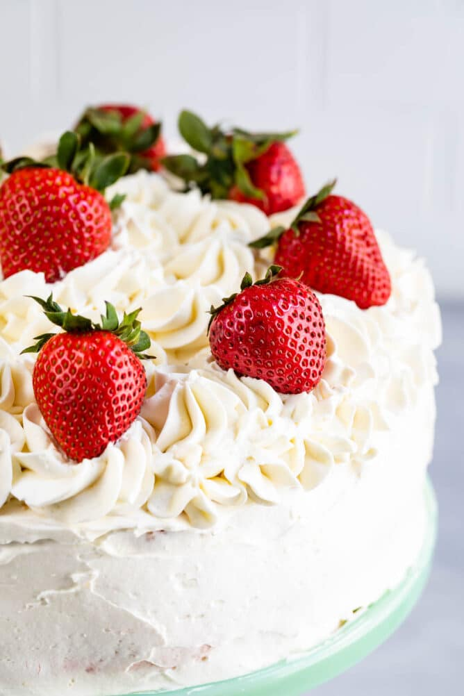 close up of cake frosted with white frosting and fresh strawberries