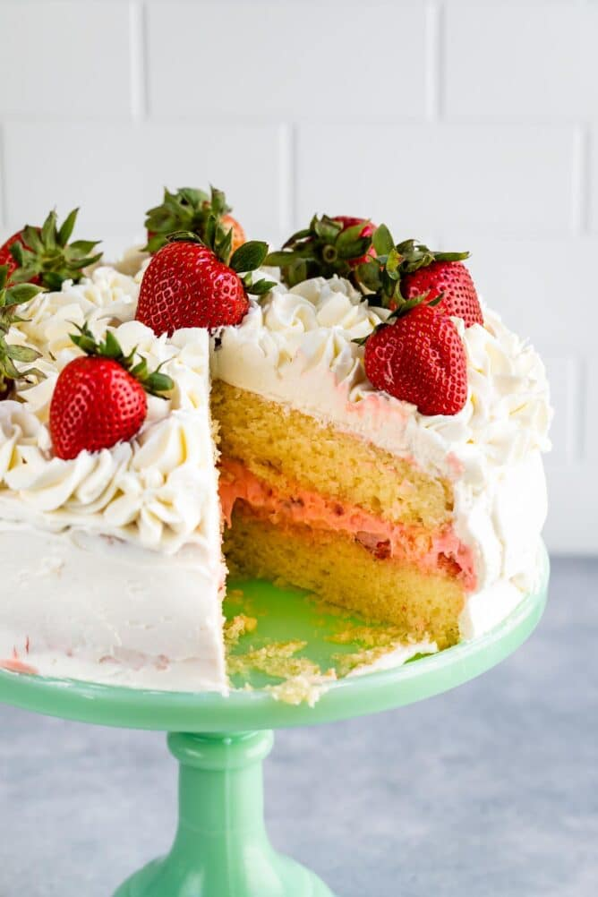 cake with slice missing showing yellow cake and pink filling inside on mint cake plate