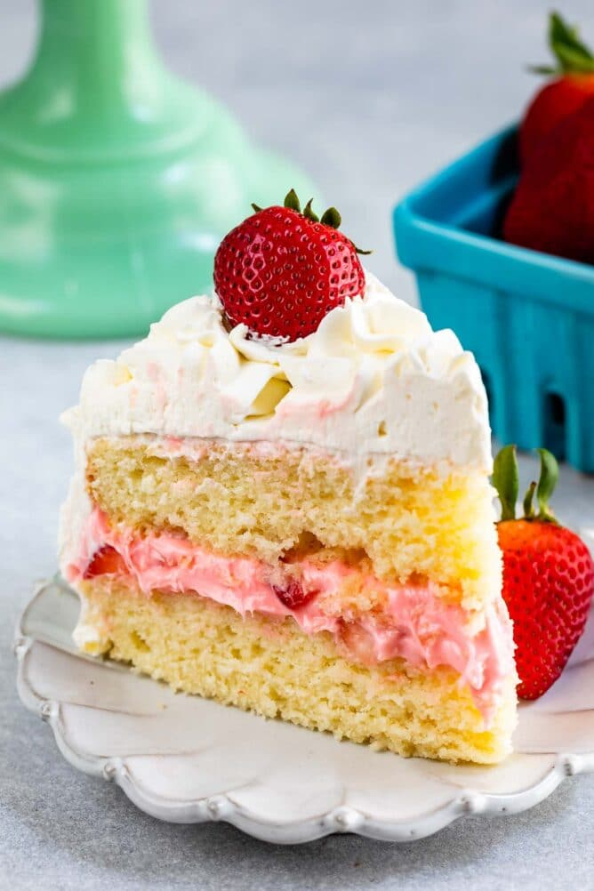 slice of strawberry shortcake layer cake on white plate with fresh berries on top