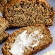 Slices of zucchini bread and front slice is lathered with butter