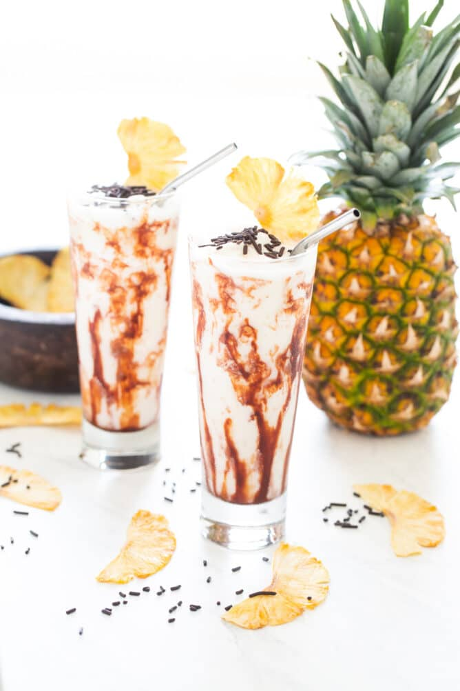 Two chocolate colada drinks with pineapple slices on top