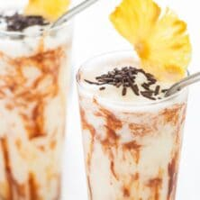 Two chocolate coladas with pineapple slices on top and recipe title on top of photo