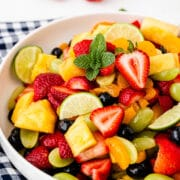 Big bowl of fruit salad on top of a checkered tablecloth