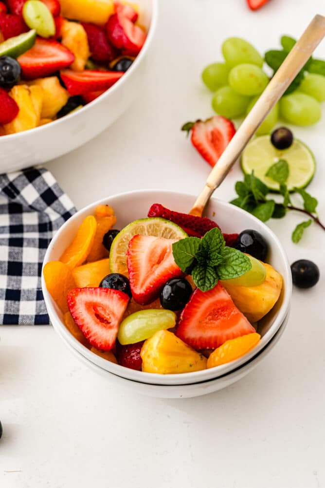 Small bowl of fruit salad with larger serving bowl in the background