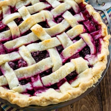 Lattice top blackberry pie with blackberries behind it and recipe title on bottom of photo