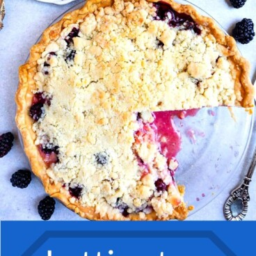 Overhead shot of blackberry pie with a crumble topping with one slice on a plate with recipe title on bottom of photo