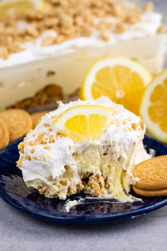 One slice of no bake lemon dessert on blue plate with one bite missing