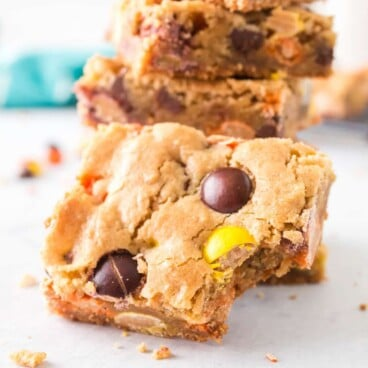 Stack of loaded cookie bars with one in front missing on bite