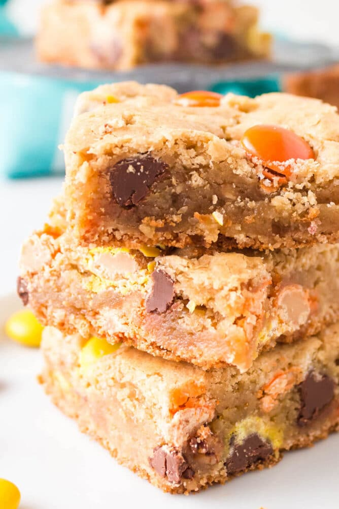 Close up shot of three loaded cookie bars stacked on top of eachother