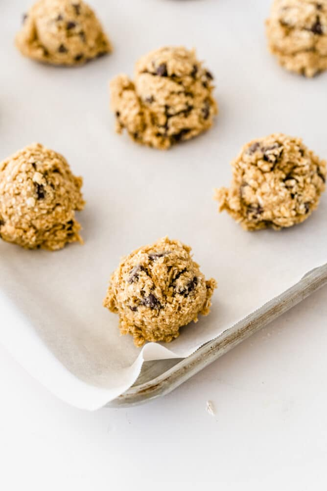 Balls of oatmeal chocolate chip cookie dough on sheet pan before being baked