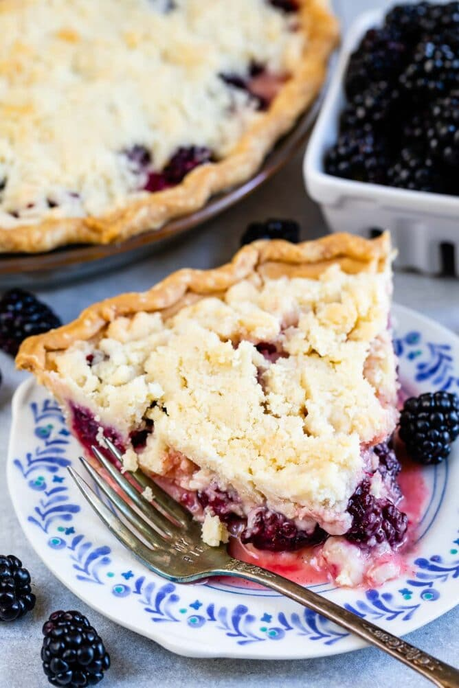 One slice of blackberry pie with crumble topping on a plate