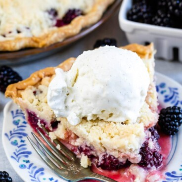 One slice of blackberry pie with crumble topping and a scoop of ice cream on top on a plate