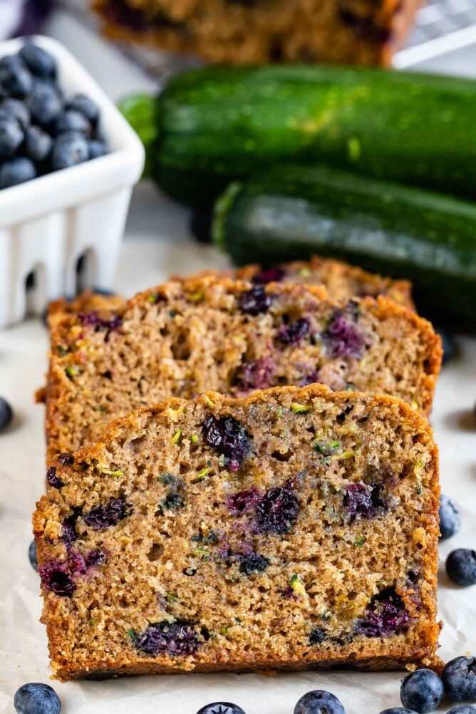 Three slices of blueberry zucchini bread with blueberries around it