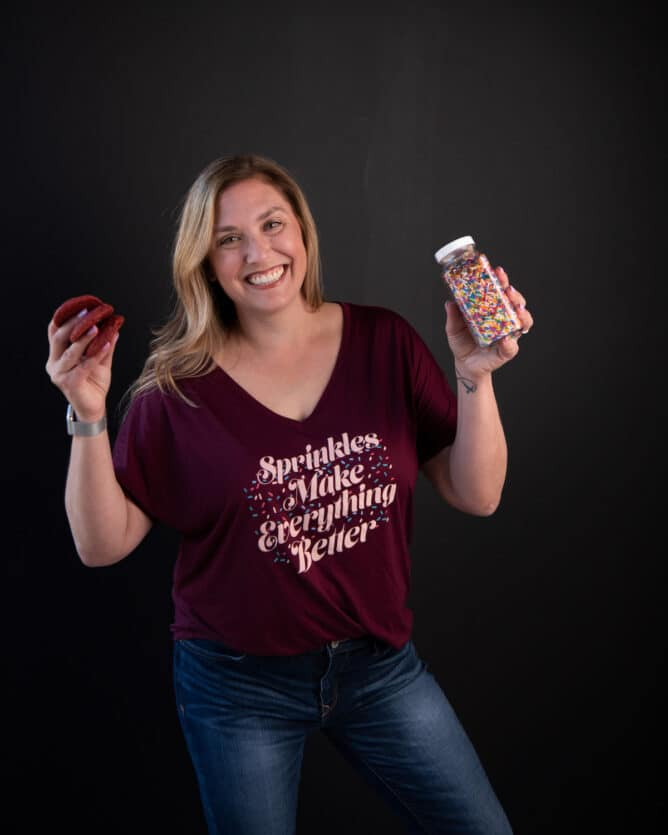 woman in maroon shirt holding sprinkles and cookies