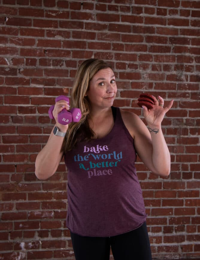 woman in purple tank holding cookies and weights
