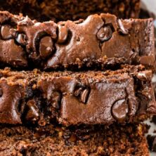 Overhead shot of sliced triple chocolate banana bread loaf with recipe title on top of image