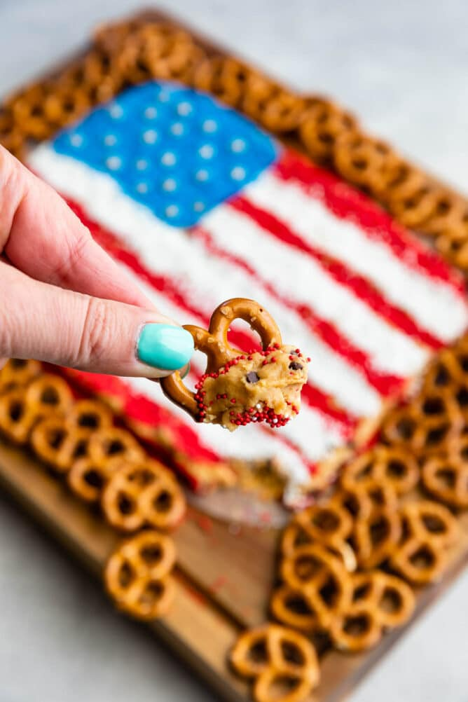 Hand holding a pretzel dipped in the peanut butter flag dip