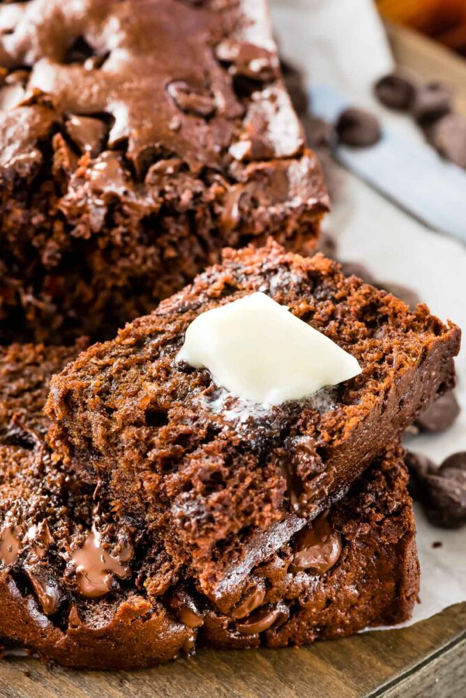 Close up of triple chocolate banana bread with end slice cut off and butter on top