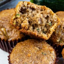Zucchini muffins with top one split in half to show inside of muffin